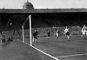 Goalkeeper Stan Hanson is rooted to the spot as Mortensen's free-kick beats him.