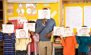 Teacher and students hold drawings over their faces