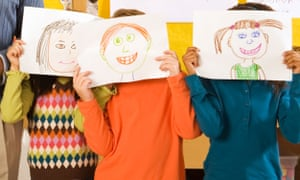 School pupils holding drawings over faces