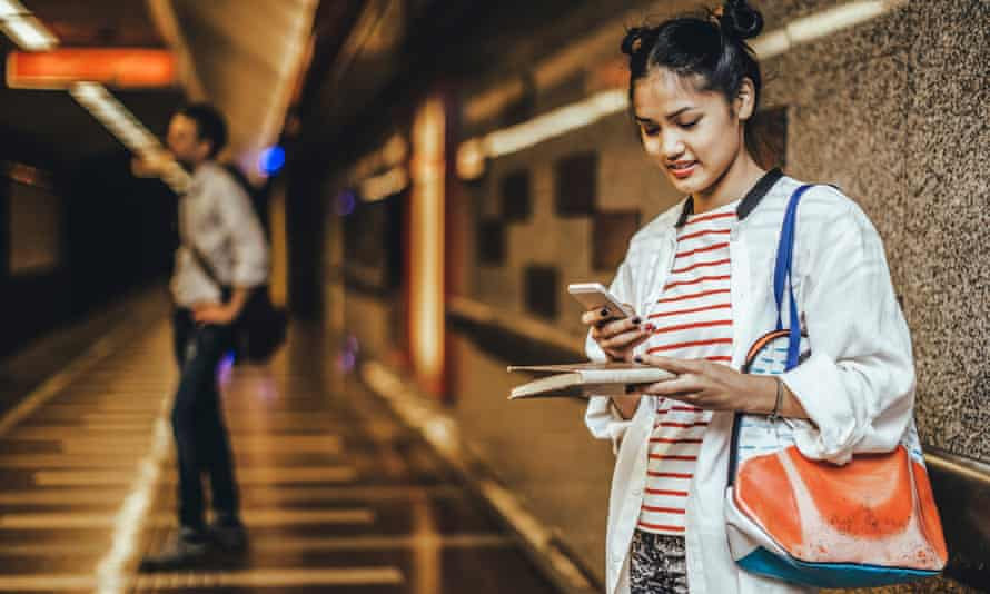 a young woman with a book checking her phone at a train station.