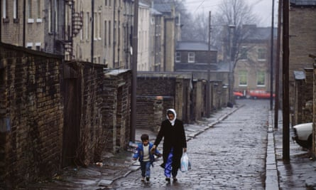 A Muslim woman and her son walk down a cobbled street in Bradford