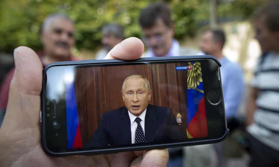Vladimir Putin speaking on TV, shown on a smartphone