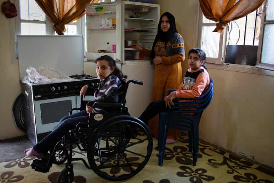 Aisha Ibrahim stands next to her nearly empty fridge with two of her three disabled children, Zam Zam and Bayan, at their new home in in Zahlé, 25 March 2021