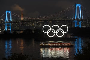 Illuminated Olympic rings are seen in front of Tokyo Tower to mark one year until the Tokyo Olympic Games.