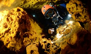 A scuba diver looks at an animal skull in the Sac Actun underwater cave system.