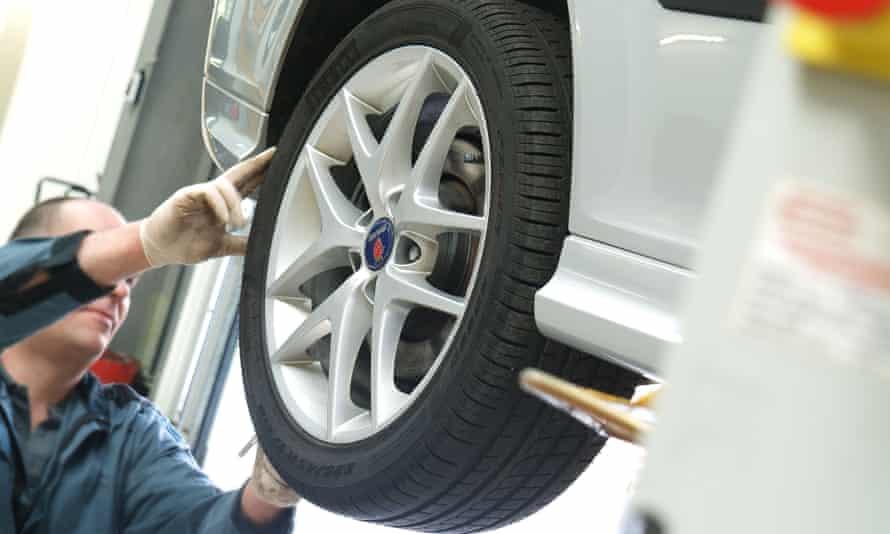 A garage mechanic checks tread depth on a tyre.