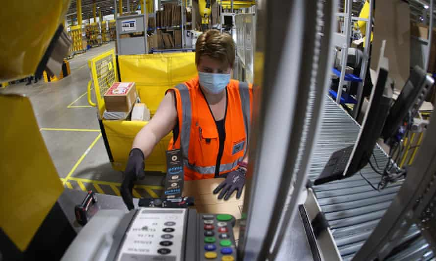 An employee prepares a package for shipment at an Amazon logistics center near Magdeburg, Germany.