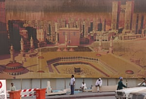 Workers stand before a hoarding showing the plan for the restoration of the Grand Mosque area.