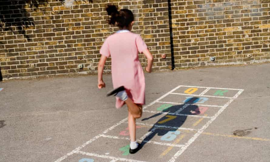 Young girl playing hopscotch in school playground