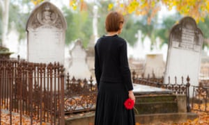 Young woman in mourning walking in cemetery in fall with red flower