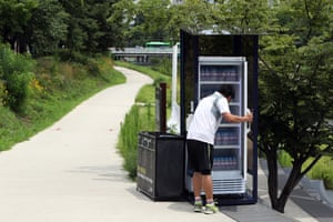 Seoul, South Korea: A resident takes a bottle of water from a refrigerator set up for villagers at a neighbourhood park during a heatwave