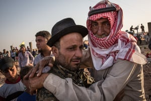 Men embrace during a funeral for fighters