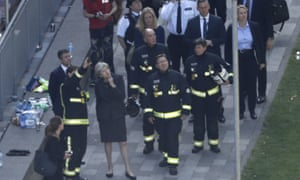 Theresa may, surrounded by emergency service personnel, at scene of Grenfell Tower fire