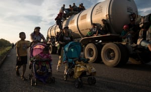 Migrants part of the caravan push strollers on the road.