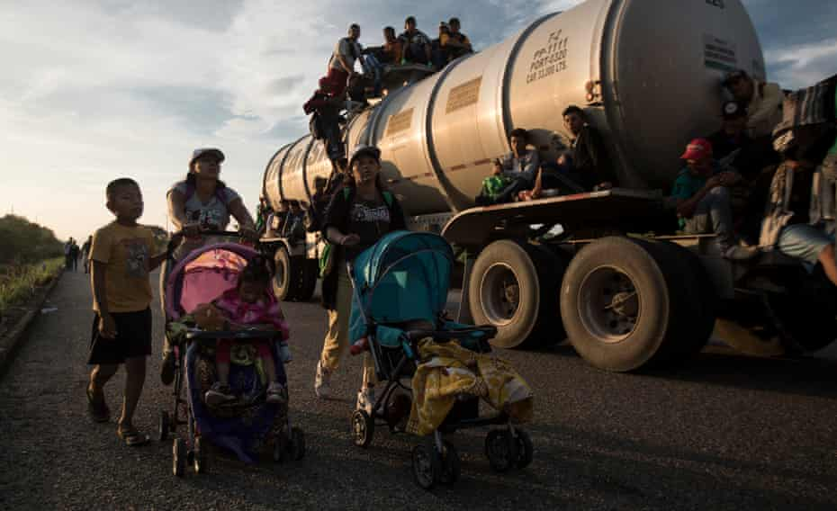 Migrants part of the caravan push strollers on the road.