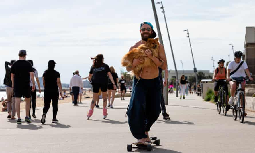 A man skates while holding his dog at Elwood beach in Melbourne