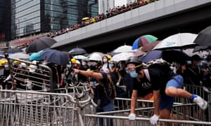 A protester mounts a metal barricade during a demonstration against a proposed extradition bill in Hong Kong