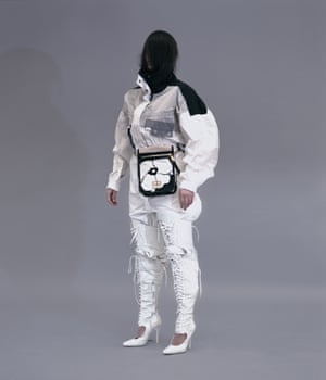 Nassia wears jumpsuit, £825, and pouch, £720, by Marc Jacobs. Top, from a selection, by Issey Miyake. Boots, from a selection, by Jeremy Scott.