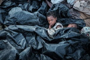 Buzi, Mozambique. Enia Joaquin Luis, 11, wakes up beside her sister Luisa, six, under plastic sheets as they shelter at the Ring ground after Cyclone Idai smashed into the coast of central Mozambique last week