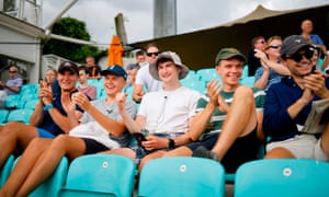 A group of friends sit together – without wearing masks – though spaces were left between rows of seats at the Oval.