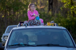 A girl sits on the roof of her family's truck while waiting for the start of a double feature at the drive-in theatre in the mountain town of Tiger, Georgia, United States