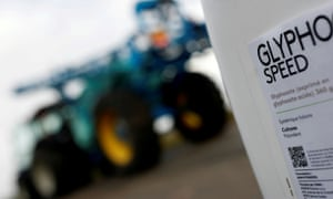 A can of glyphosate weedkiller is seen in front of a tractor