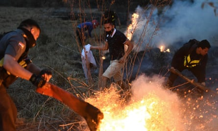 Members of Paraguay's highway patrol and local residents try to extinguish a fire on 27 September in San Bernardino, east of Asuncion, Paraguay.