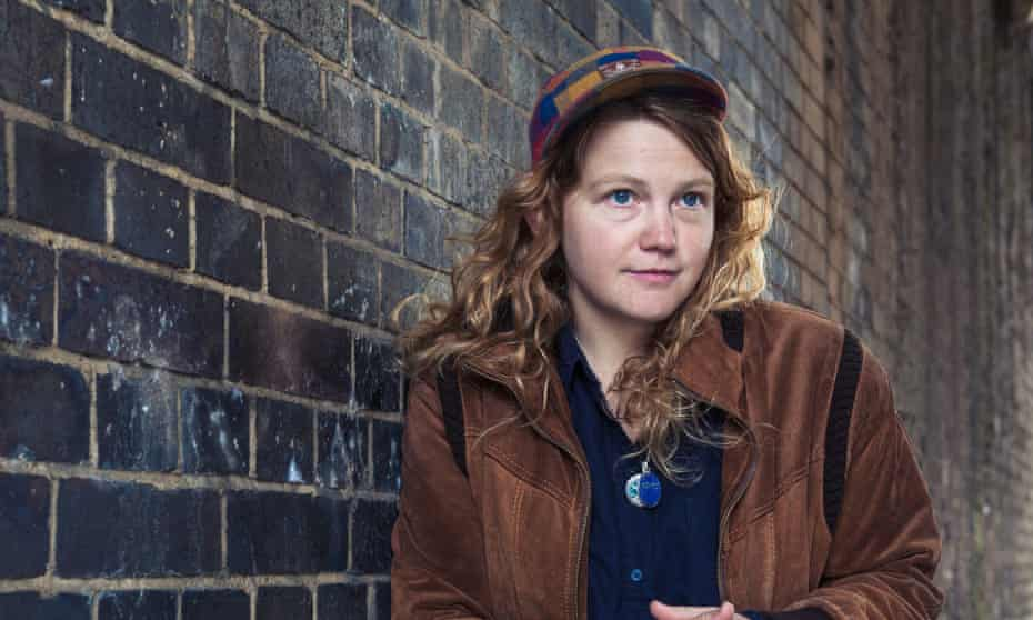 Kate Tempest in a cap and jacket leaning against a brick wall