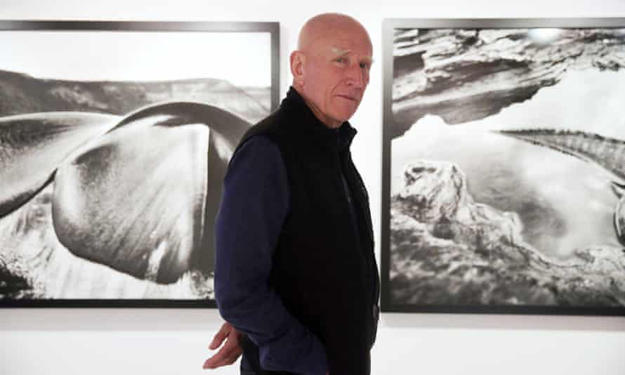 Brazilian photographer Sebastião Salgado with images from his Genesis exhibition at a gallery in Hong Kong, December 2013.