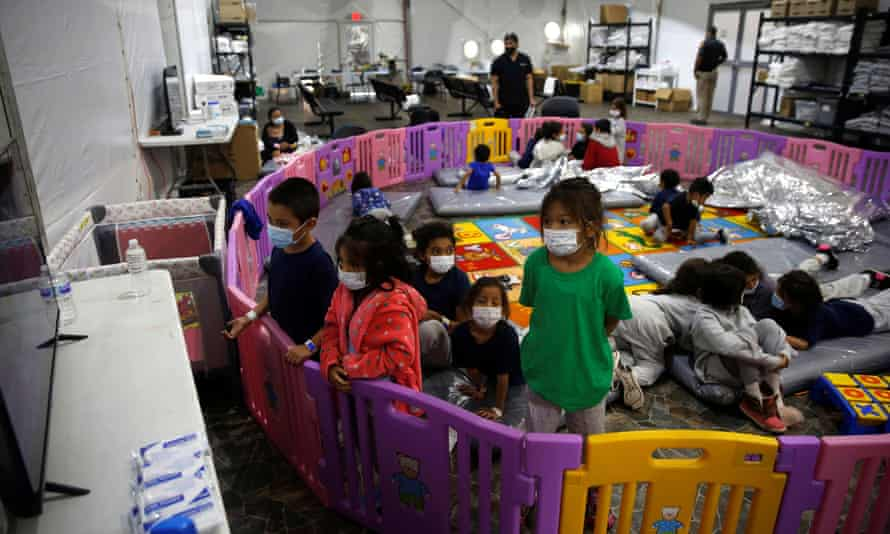Unaccompanied migrants from ages three to nine watch TV inside a playpen at the facility in Donna, Texas, on 30 March.