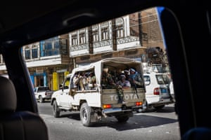 The photograph is taken from inside a car. Outside the car window we can see a  military truck of Houthi militiamen.