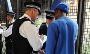 Metropolitan Police officers question a man during a stop and search operation.