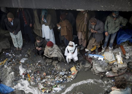 People shelter under the Pul-e Sokhta bridge in western Kabul, during a police round up of suspected drug addicts.