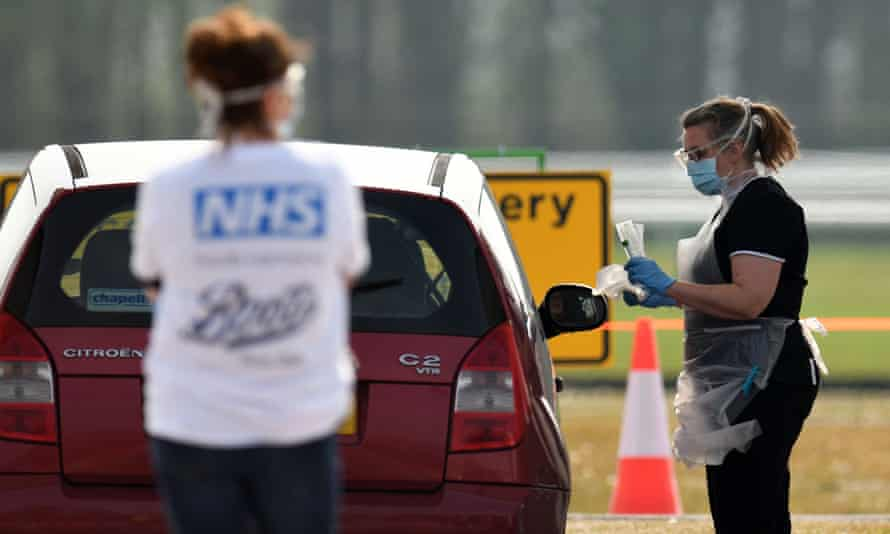 A medical worker tests an NHS worker at a drive-in testing station in Merseyside.