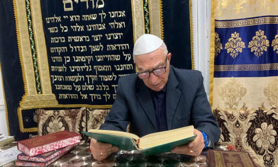 Abram Iskhakov, the president of the Bukhara Jewish Community, reads during an evening service in Bukhara, Uzbekistan.