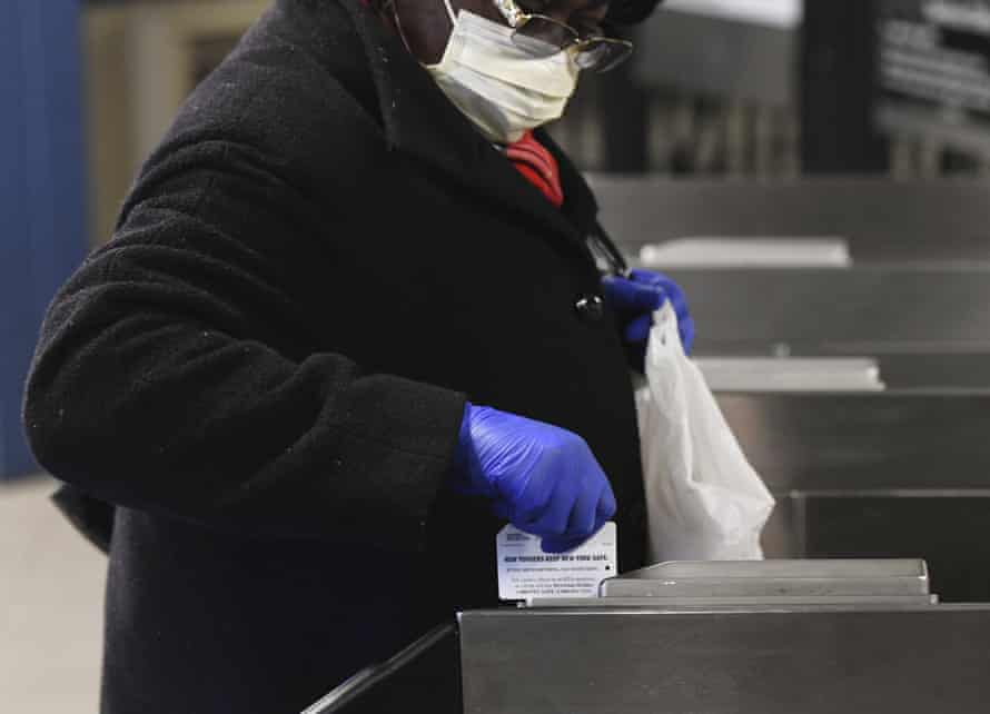 A woman wears gloves while swiping her fare card in the New York subway.