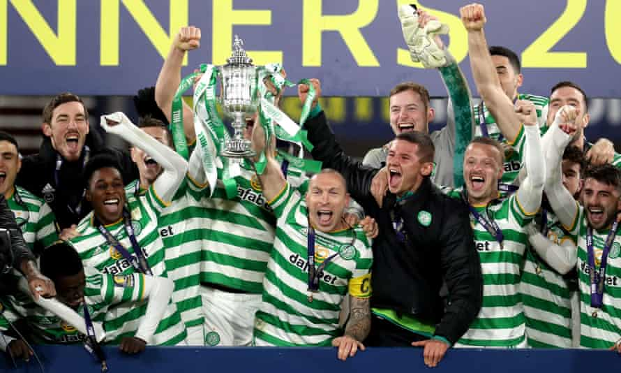 The Celtic players celebrate with the trophy after defeating Hearts in the Scottish Cup final.