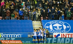 Wigan players mob Will Grigg after his 79th-minute effort put them ahead against high-flying Manchester City.