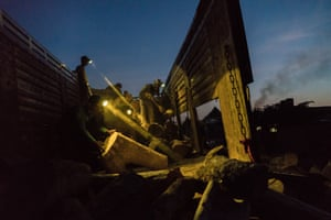 A truck full of wood is unloaded at night in a brick kiln located in the periphery of Phnom Penh