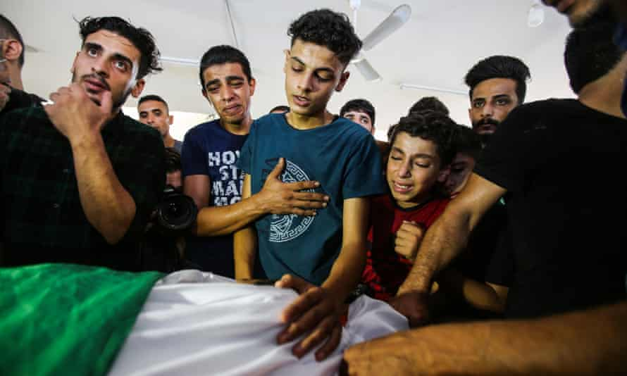 Los familiares del niño palestino de 12 años Omar Hassan Abu al-Nil lloran su cuerpo cubierto con la bandera palestina.