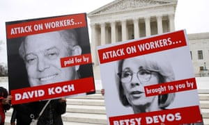 Members of the American Federation of Teachers hold up signs depicting Education Secretary Betsy DeVos and David Koch, while protesting in support of unions outside of the supreme court on 26 February.