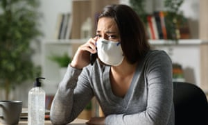 worried woman wearing face mask takes a call