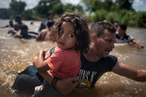 Luis Acosta holds 5-year-old Angel Jesus, both from Honduras, as a caravan of migrants from central America moving towards the US cross through the Suchiate River into Mexico from Guatemala. 29 October, 2018.