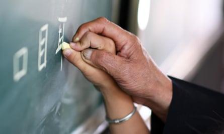 a teacher helps a child write