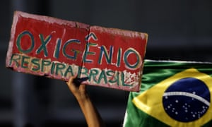 "A demonstrator hold poster with a message that reads in Portuguese ""Oxygen, Breathe Brazil,"" during a protest against the government's response in combating COVID-19 and demanding the impeachment of Brazil's President Jair Bolsonaro, in Brasilia, Brazil, Sunday, Jan. 24, 2021. (AP Photo/Eraldo Peres)"