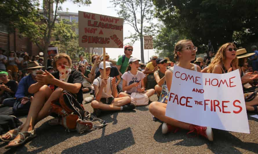 Protesters holding placards demand climate action outside Kirribilli House in Sydney on Thursday