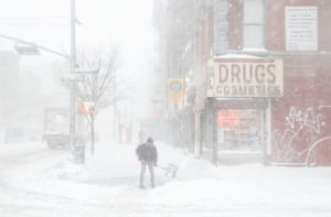 A man shovels snow in the East Village as a storm hit New York.