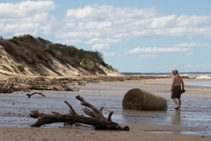 A man inspect one of the beached bales