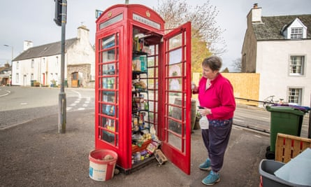 Susan Crawford, a founder of the phone box community food larder in Muthill, Perthshire, checks the provisions.