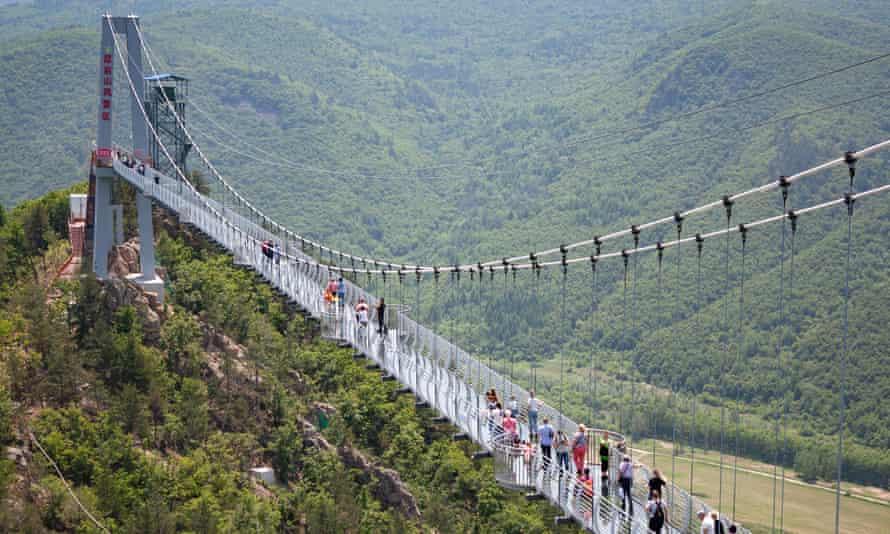 Tourists walk on the glass bridge in Longjing in 2019.